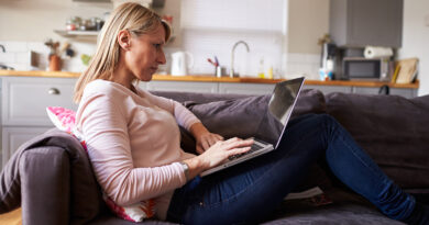 Woman Relaxing On Sofa Using Laptop In Modern Apartment